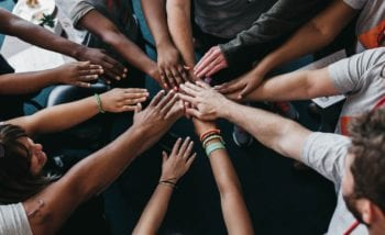 Group of people putting hands in the middle